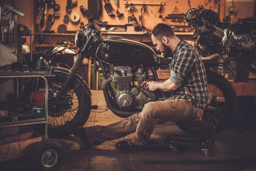 Mechanic building vintage style cafe-racer motorcycle  in custom
